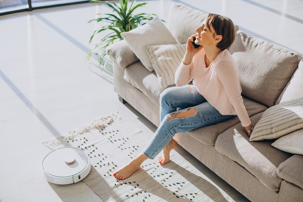 Woman relaxing on sofa while robot vacuum cleaner doing housework
