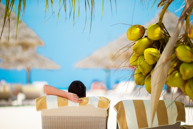 Woman relaxing on sun lounger under a coconut tree