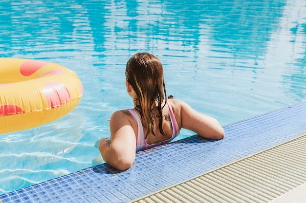 Woman relaxing next to swimming pool