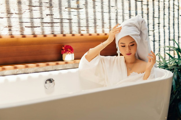 Woman relaxing in tub under sunshine
