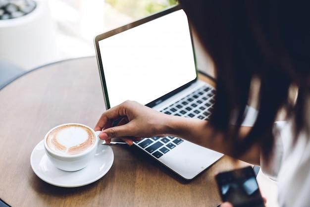 カフェに座ってコーヒーを飲みながら椅子に座っている白いモックアップ空白の画面を持つラップトップコンピューターの技術を使用してリラックスした女性