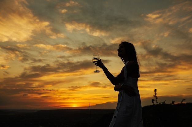 ゴージャスな夕日を眺めながらリラックスできる女性。