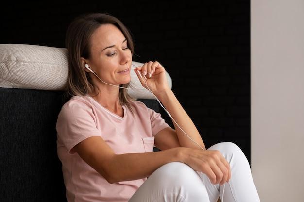 Женщина расслабляется, слушая музыку дома