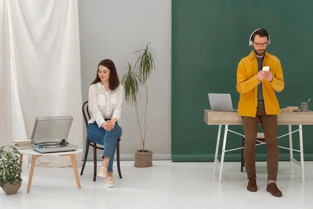 Donna che si distende durante la lettura di libri e uomo utilizzando il cellulare