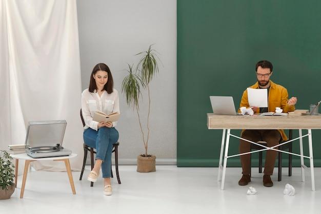 Donna che si distende durante la lettura di libri e uomo che lavora al computer portatile