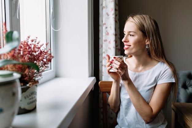 Женщина расслабляется с кофе у окна
