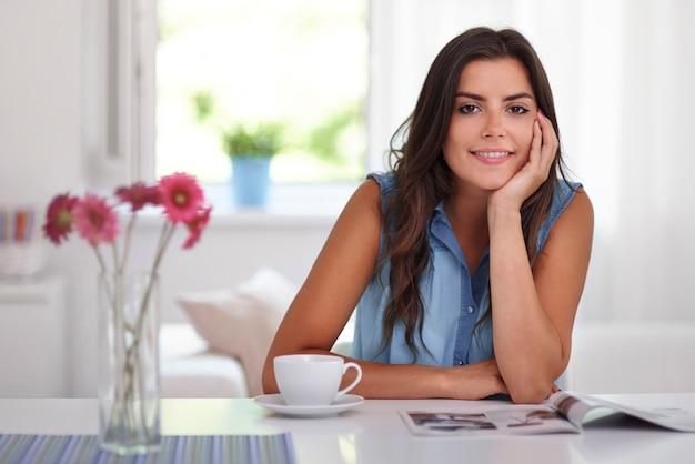 Donna che si distende con giornale e caffè