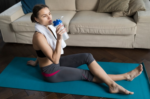 Woman relaxing on yoga mat while drinking water