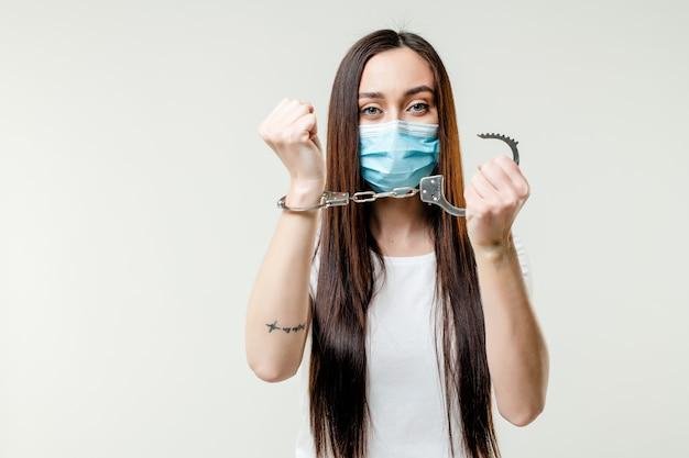 Woman releasing herself from handcuffs wearing mask