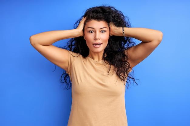 女性は何かを思い出し、頭に手をつないで、ショックを受けました。孤立した青い壁