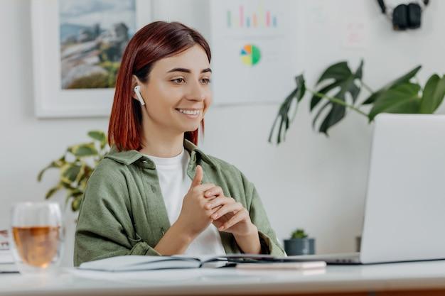Женщина, удаленно работающая дома с ноутбуком молодой предприниматель, разговаривает через беспроводные наушники