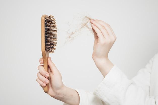 Женщина удаляет пучок волос с помощью деревянной расчески на легкой стене проблемы со здоровьем.