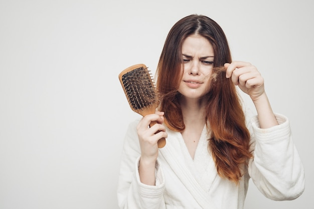 Woman removes curls of hair from a comb loss of health problems model