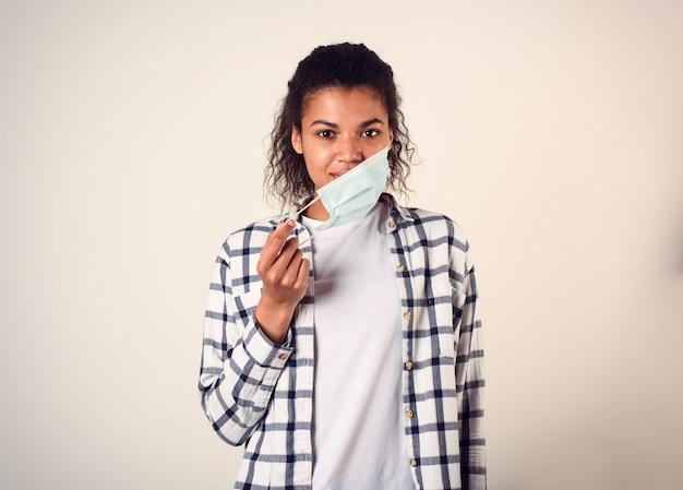 Женщина снимает маску с лица. концепция пандемии коронавируса covid-19