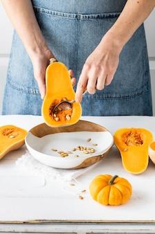 キッチンでバターナッツかぼちゃの種を取り除く女性