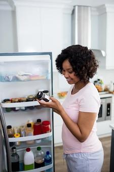 Женщина вынимает стеклянную банку из холодильника