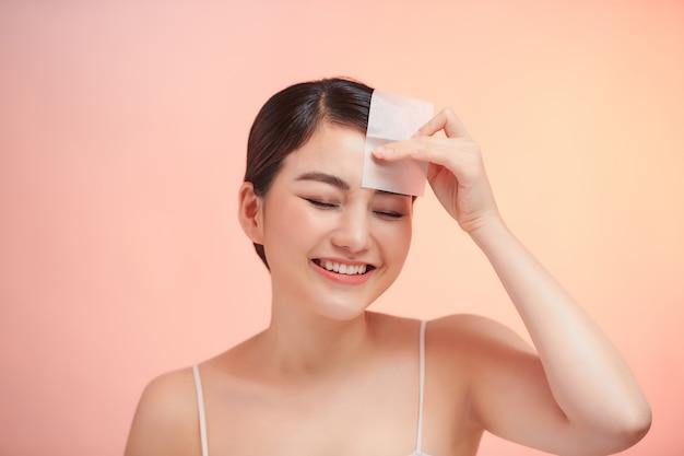 あぶらとり紙を使用して顔から油を取り除く女性。