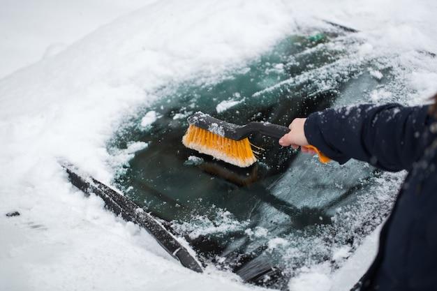 車のフロントガラスから除雪する女性