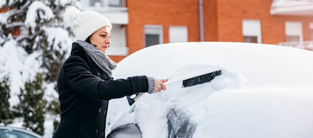 Woman removing snow from the car