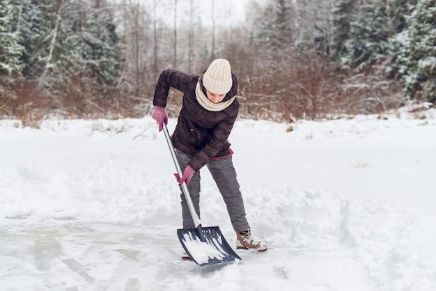 冬にシャベルで除雪する女性。