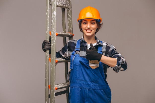 Woman repairer with ladder in a uniform isolated