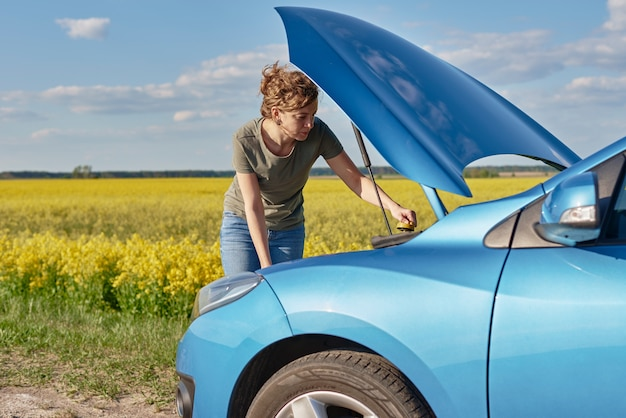 開いたボンネットで壊れた車を修理する女性