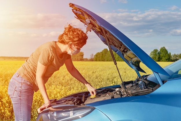Woman repairs broken car with the open hood on the road