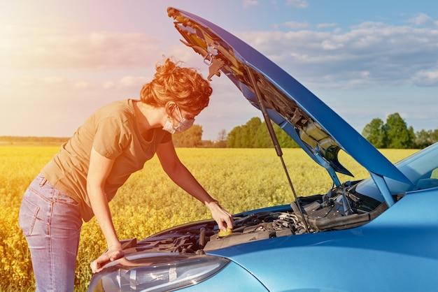 道路上のフードを開けて壊れた車を修理する女性