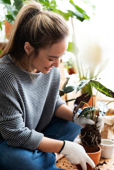 Woman repotting a houseplant inside of her house