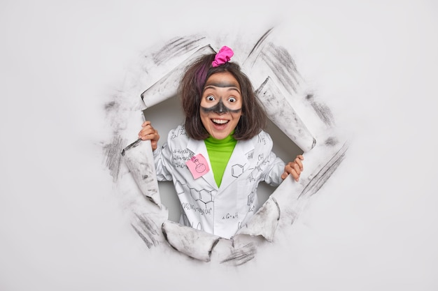 Женщина-исследователь грязная после проведения химического эксперимента, одетая в медицинский халат, пробивает бумагу