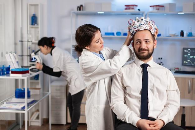 Женщина-исследователь надевает гарнитуру для сканирования мозговых волн пациенту, проводящему эксперименты с использованием лабораторных мониторов для исследования мозга. человек сидит на стуле, пока ученый настраивает устройство, исследующее нервную систему