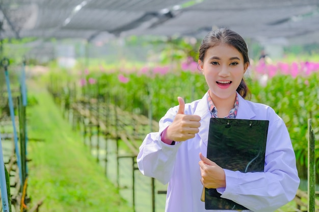 Woman researcher in a white dress, thumbs up and explores the garden