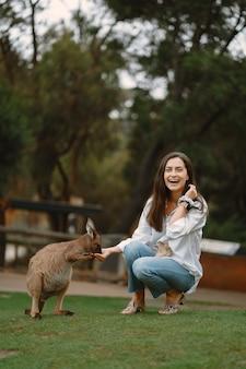 La donna nella riserva sta giocando con un canguro