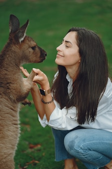 Woman in the reserve is playing with a kangaroo