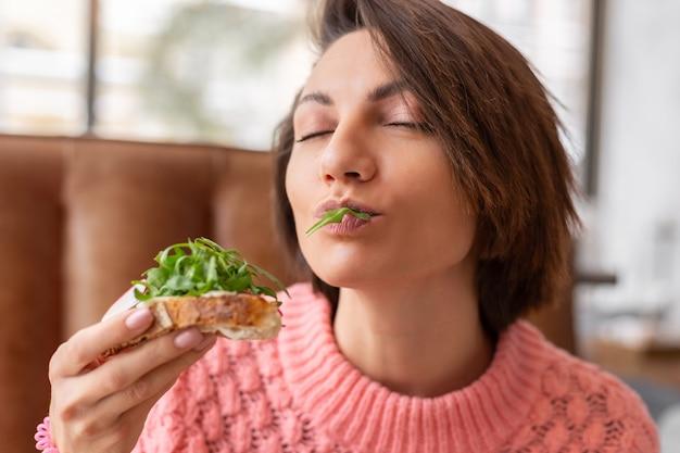 La donna in un ristorante in un accogliente maglione caldo sana colazione con pane tostato con rucola e salmone