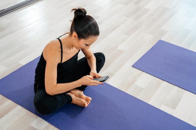 携帯電話で自宅のトレーニングの後に休んでいる女性。ヨガを練習した後の若いスポーティな女性、運動を中断し、ヨガマットでリラックスし、携帯電話でテキストメッセージを送信し、スマートフォンを持っています