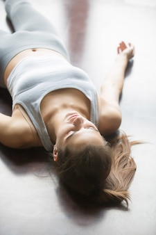 Woman resting after practicing yoga at home