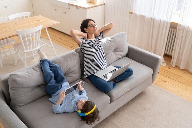 ノートパソコンでホームオフィスから仕事の後に休んでいる女性は、タブレットで遊んでいるソファの子供に座っています。封鎖。