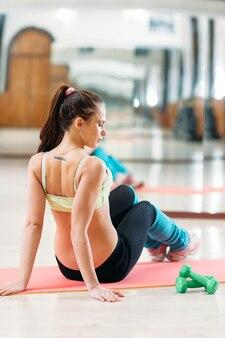 Женщина отдыхает после тренировки в тренажерном зале