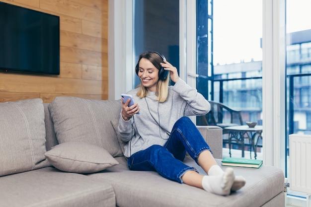 Женщина отдыхает дома, слушая веселую музыку в наушниках