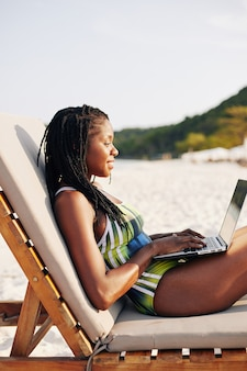 Woman resting on beach and working on laptop