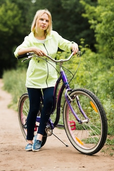 Woman resting on bicyle on forest road