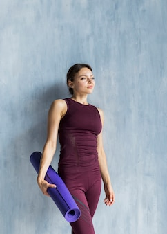 Woman resting by the wall while holding a yoga mat