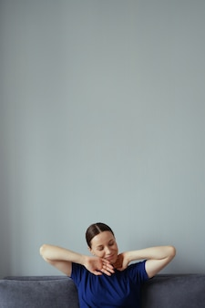 Woman resting on the couch in the living room and stretching her arms