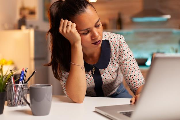 늦은 밤 마감 시간 동안 집 부엌에서 일하는 동안 눈을 쉬고있는 여자