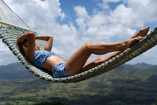 Woman resting in hammock outdoors view of the mountains vacation and travel concept