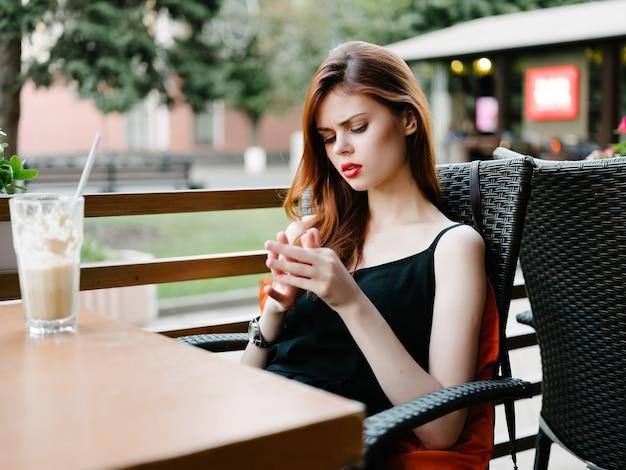 朝食を社交する屋外の夏のカフェで休んでいる女性