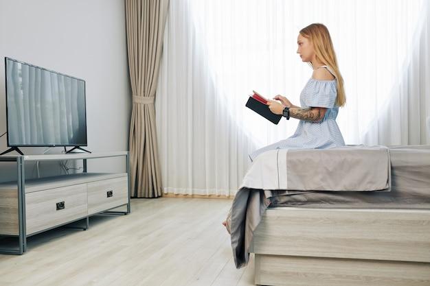 テレビの前の寝室で休んでいる女性