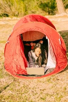 텐트에서 쉬고 노트북을 사용하는 여자