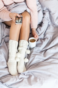 Женщина отдыхает, держа ноги в теплых носках на кровати